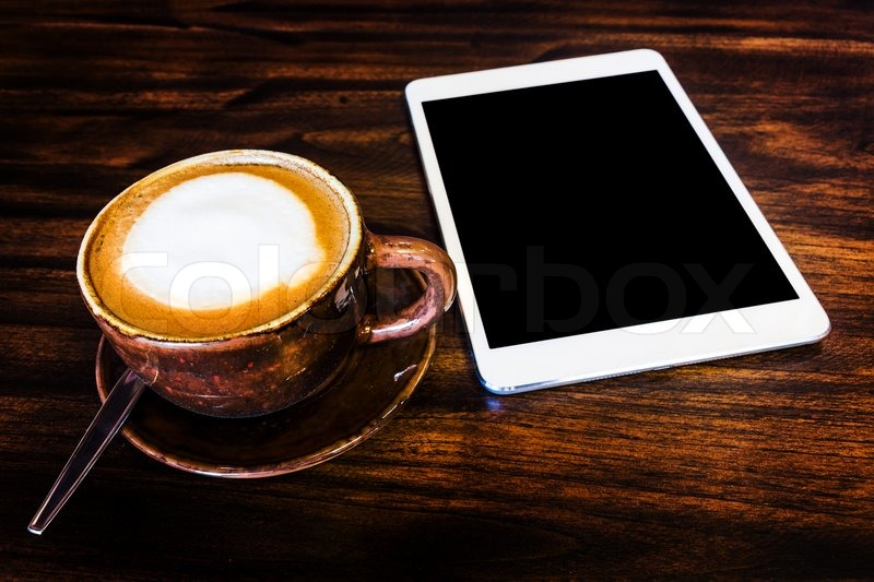 digital tablet and coffee cup on wooden table | stock photo