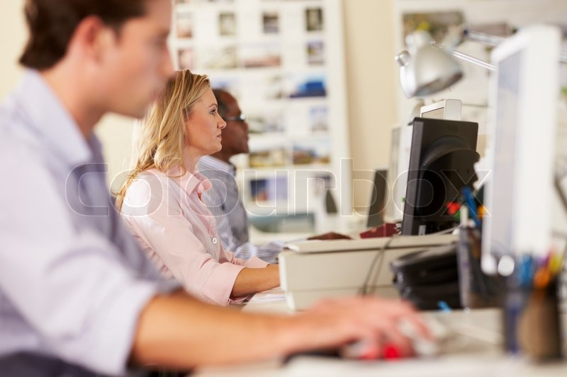 Stock image of 'Workers At Desks In Busy Creative Office'