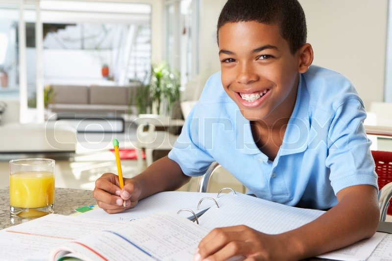 Boy Doing Homework In Kitchen, stock photo