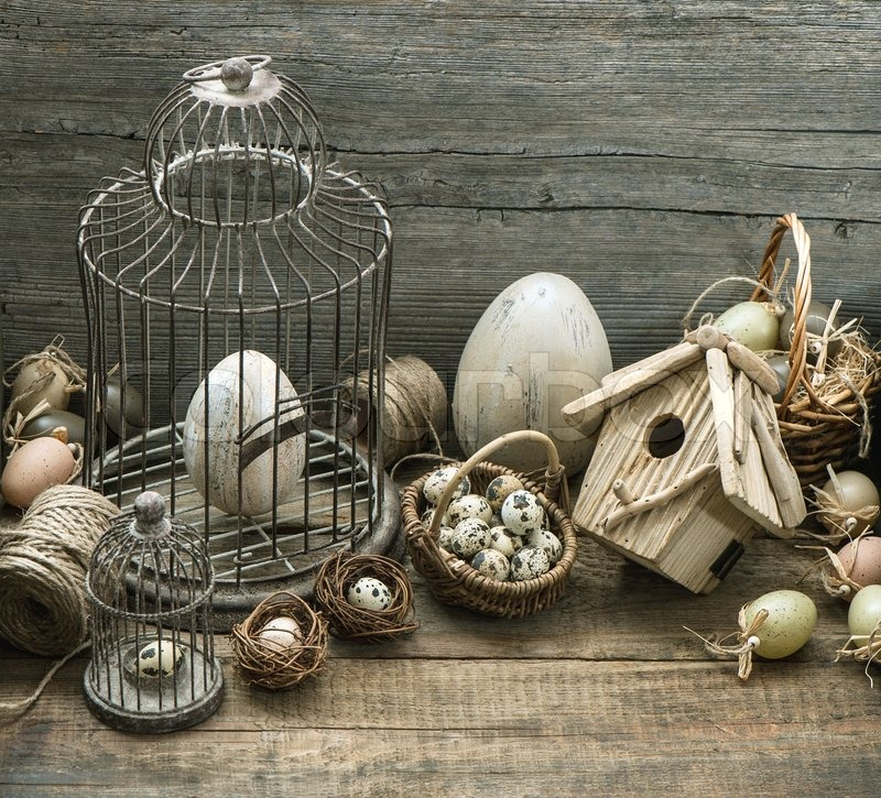 Stock image of 'vintage easter decoration with eggs, birdhouse and birdcage. nostalgic still life home interior. wooden background'