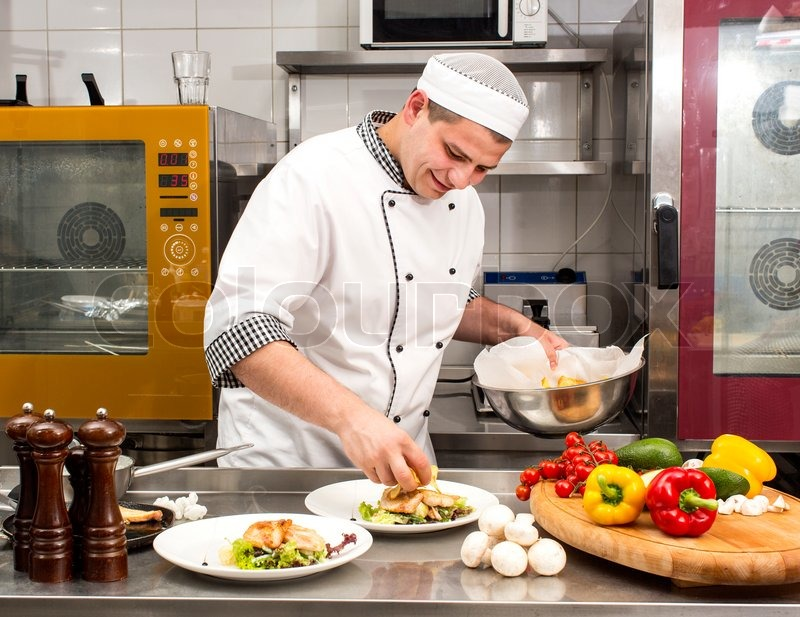 chef preparing food in the kitchen at the restaurant stock photo