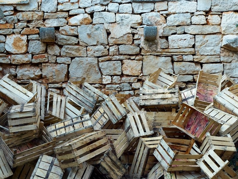Empty wooden boxes of grapes thrown to stone wall, stock photo