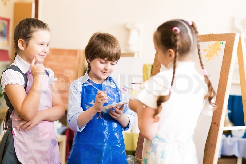 Children draw pictures of easels, drawing lesson, stock photo