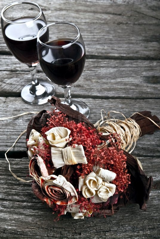 Wine bottle on a wooden table and dry flower wedding bouquet on vintage old wood, stock photo