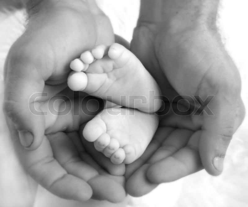 Stock image of 'Baby's feet in daddy's hands'