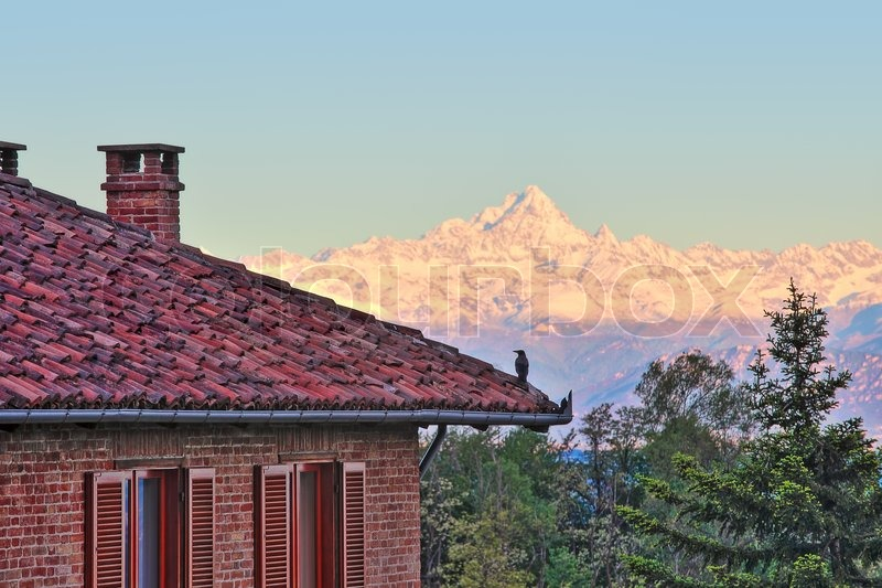 Delightful Red Brick House With Tiled Roof And Snowy Peaks Of Monviso Mountain Part Of  Italian Alps On Background In Piedmont, Northern Italy.