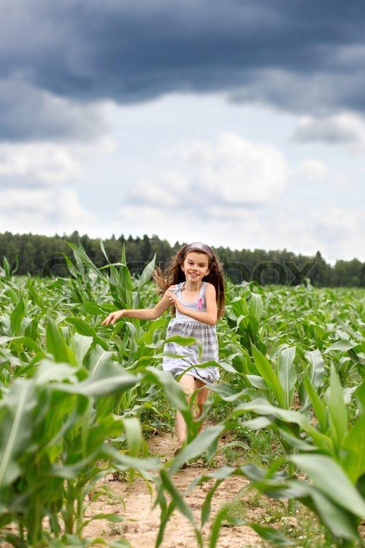 Joyful Little Girl Running Through The Corn Field Stock