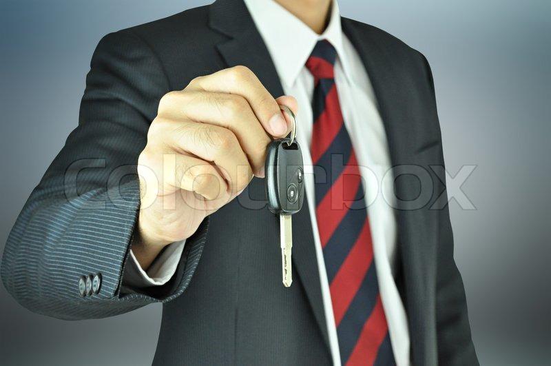 Businessman giving a car key, stock photo