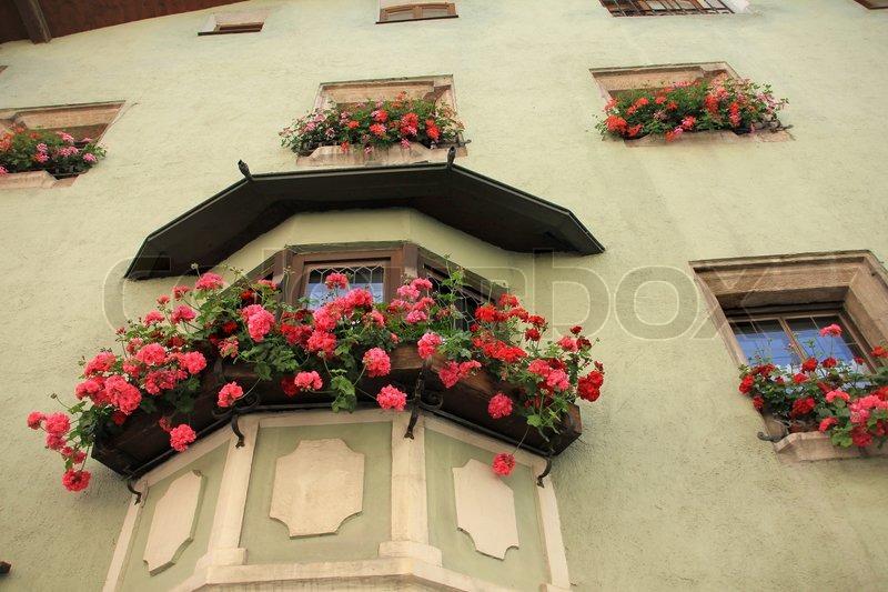 Rote und Rosa Geranien in den Blumenkästen an der Wand des Hauses ...