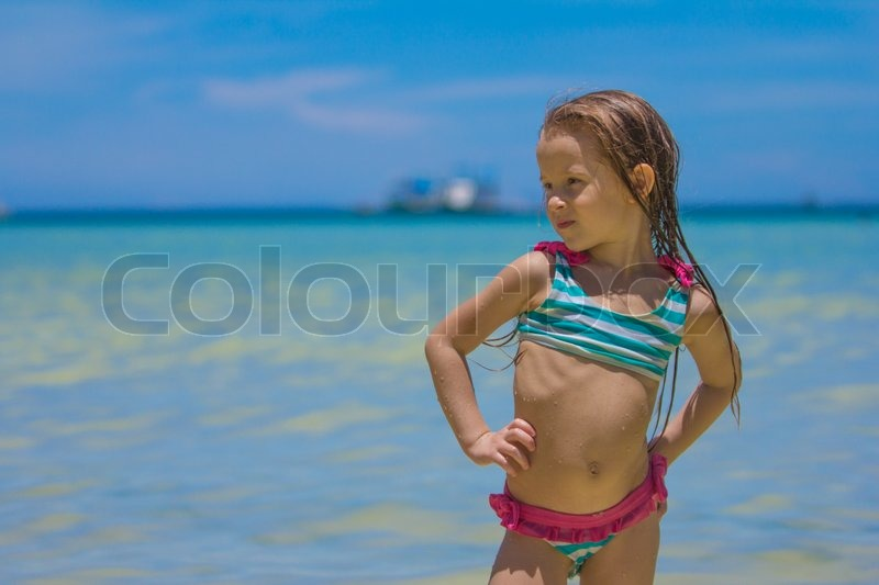 Beautiful Little Girl Standing In Water At The Beach