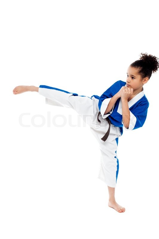 young kid kicking in the air while practicing karate stock photo