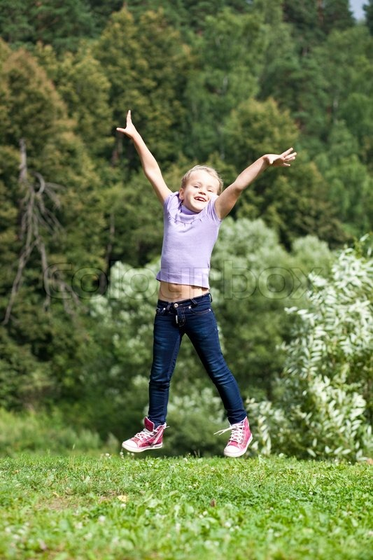 Happy Little Girl Jumping In Summer Day Stock Photo