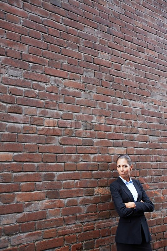 Woman by brick wall, stock photo
