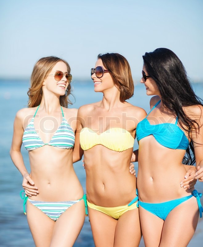 girls in bikinis walking on the beach stock photo colourbox