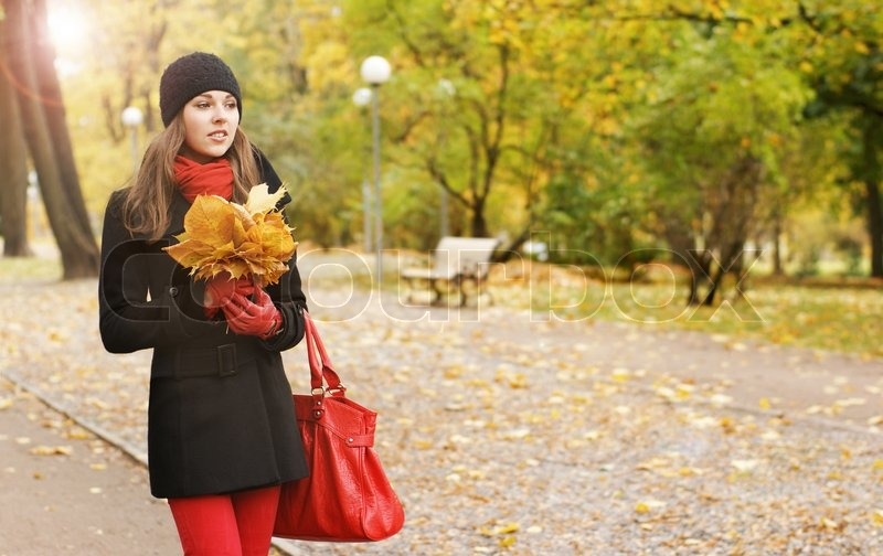 36009c23ae Stock image of  A happy woman in autumn clothes on a park background