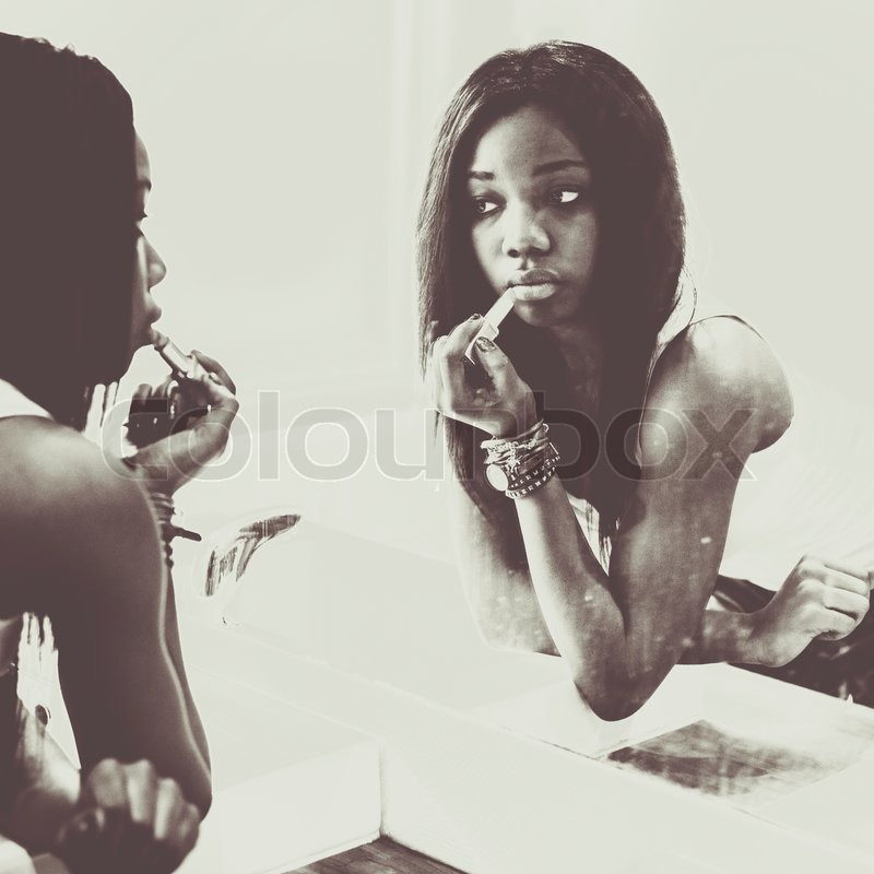 African ame3rican woman putting on lipstick in front of mirror stock photo colourbox