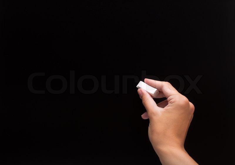 blackbohand writing something with white chalk on a blank
