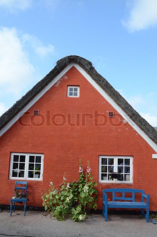 Blå stor og blå bænk foran rød kalket hus med stråtag og hvide ...