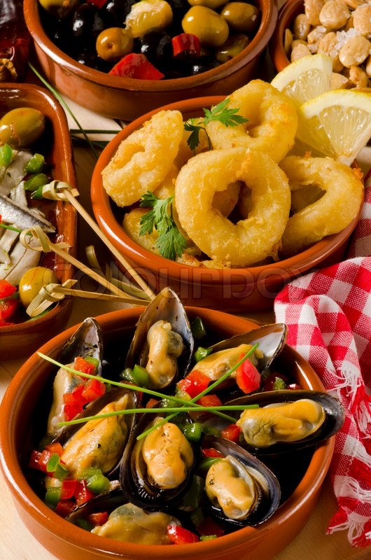 Spanish cuisine. Assortment of Tapas including Marinated Olives, Mussels in Sauce and Fried Squid Rings, stock photo