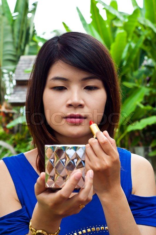 Beautiful Asian woman making up, stock photo