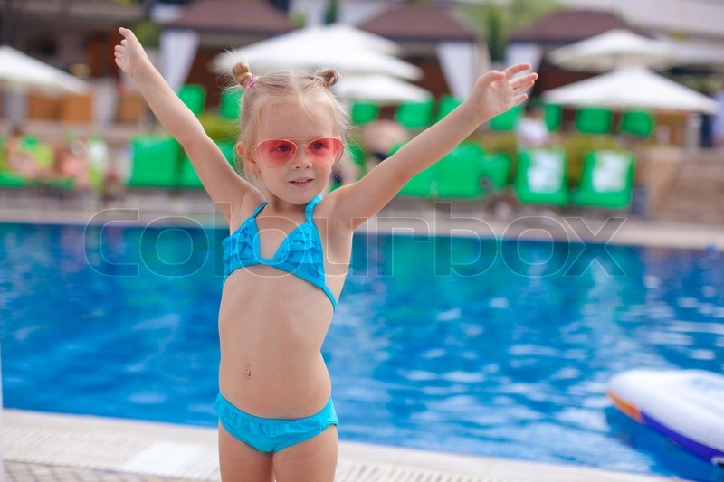 Beautiful little girl spread her arms standing near
