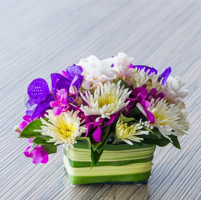 Flower bouquet of vanda, orchid, chrysanthemum on wood table, stock photo