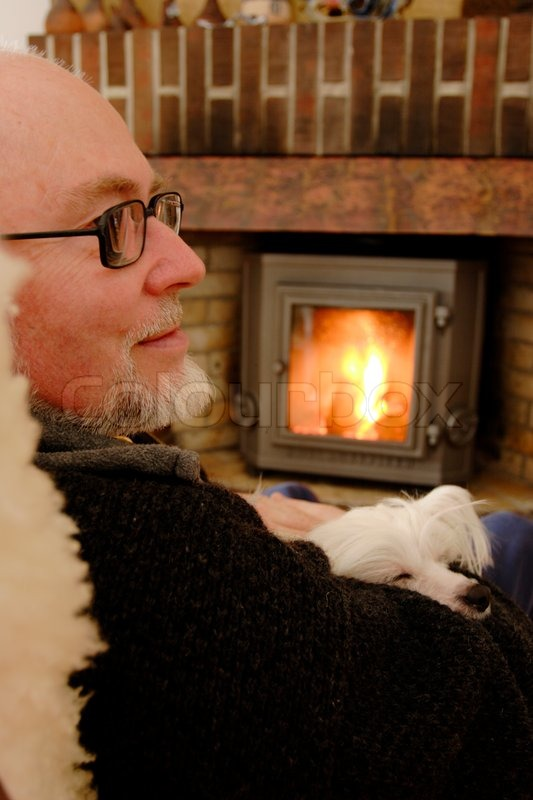 Elderly man in livingroom relaxing with small dog in his arms ...