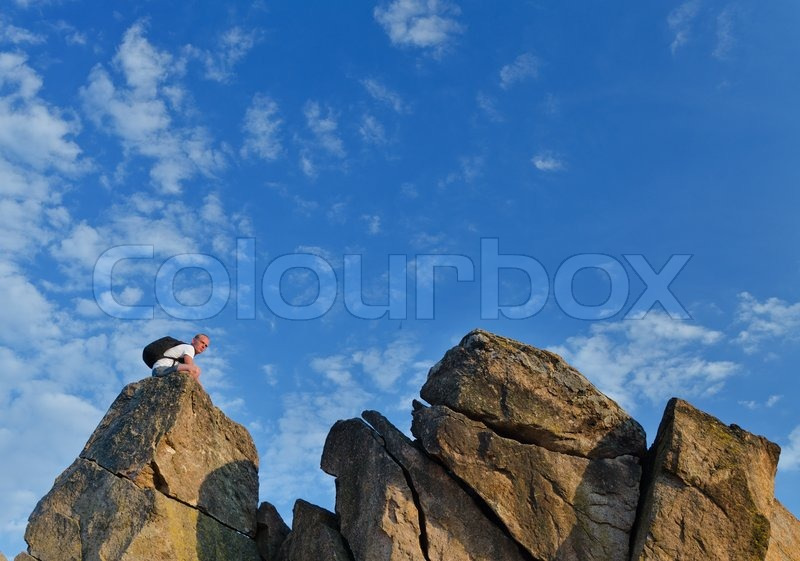 Stock image of 'Backpacker on a distant rocky mountain peak'