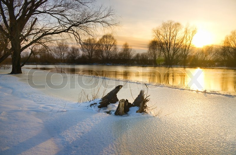 Stock image of 'Sunset over frozen river in winter'