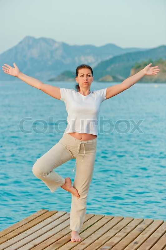 Girl standing on one leg with arms outstretched to the sides, stock photo