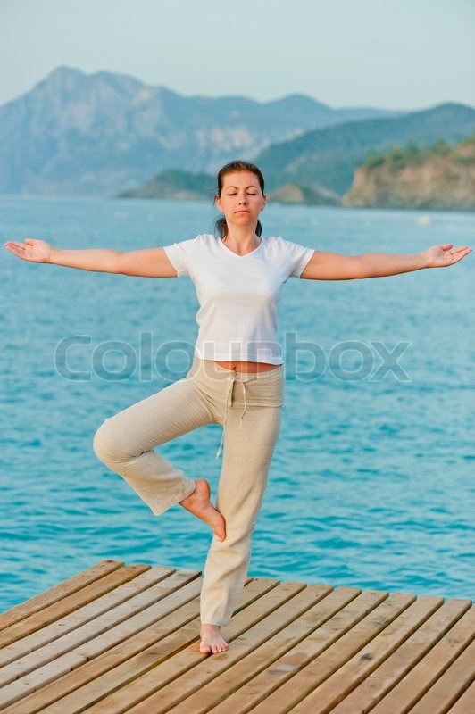 Girl by holding a balance while standing on one leg on pier, stock photo