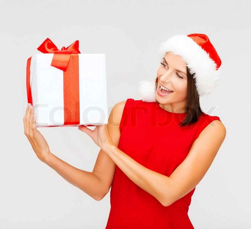 Christmas, x-mas, winter, happiness concept - smiling woman in santa helper hat with gift box, stock photo