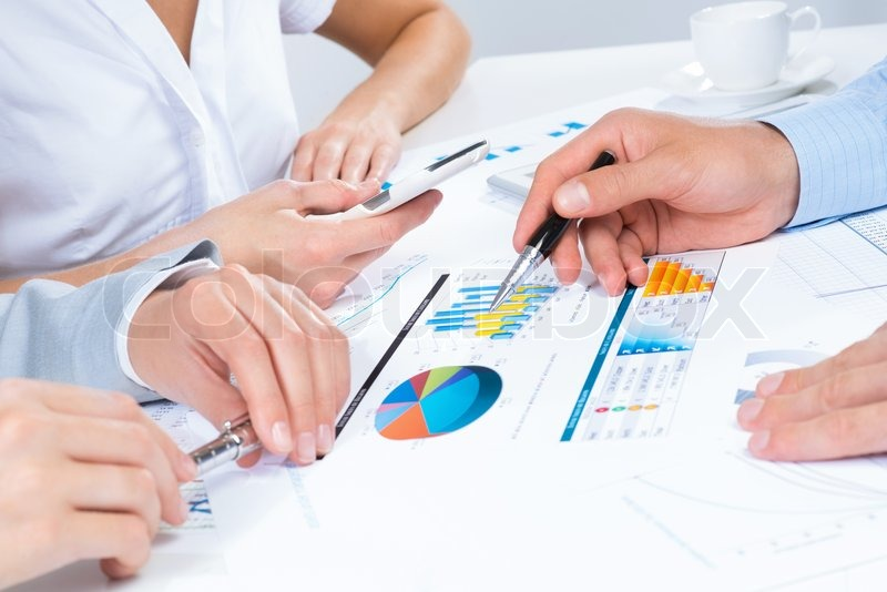 Business people discuss meeting targets, sitting at the business table with documents, stock photo