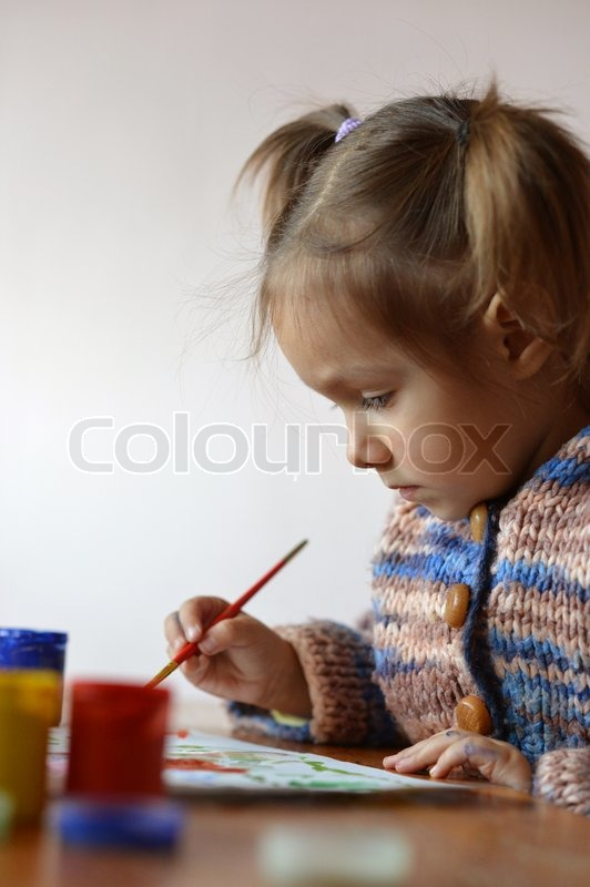 Portrait of a cute baby draws, stock photo