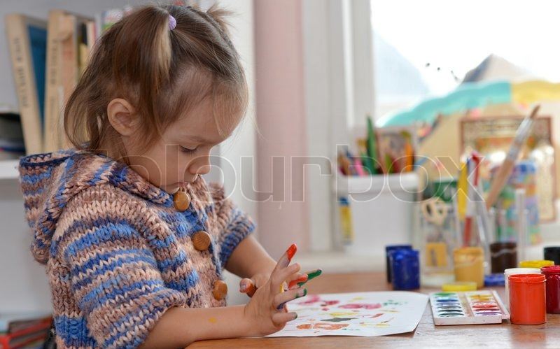 Portrait of a nice baby draws paints at the table, stock photo