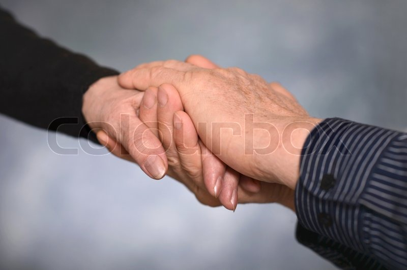 Concept shoot of friendship and love of man and woman: two hands over gray background, stock photo
