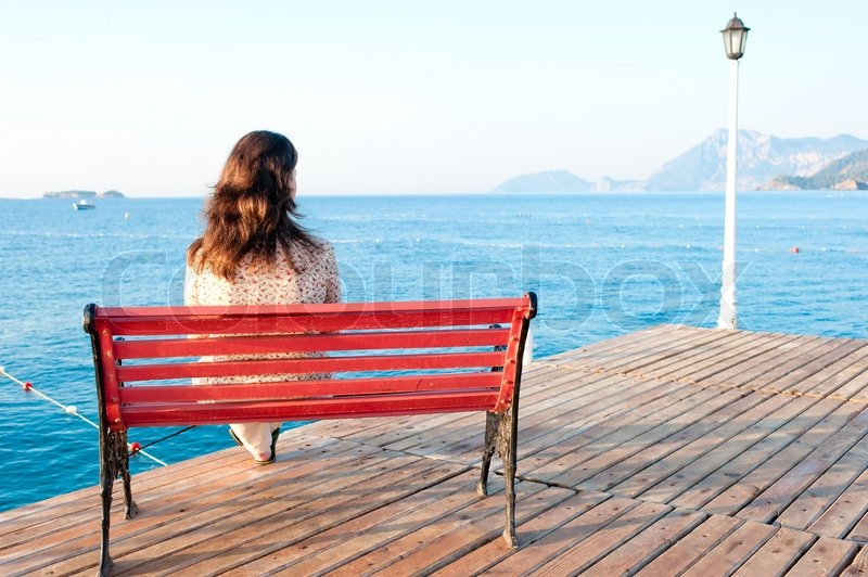 Girl sitting on a bench on the pier at     | Stock image