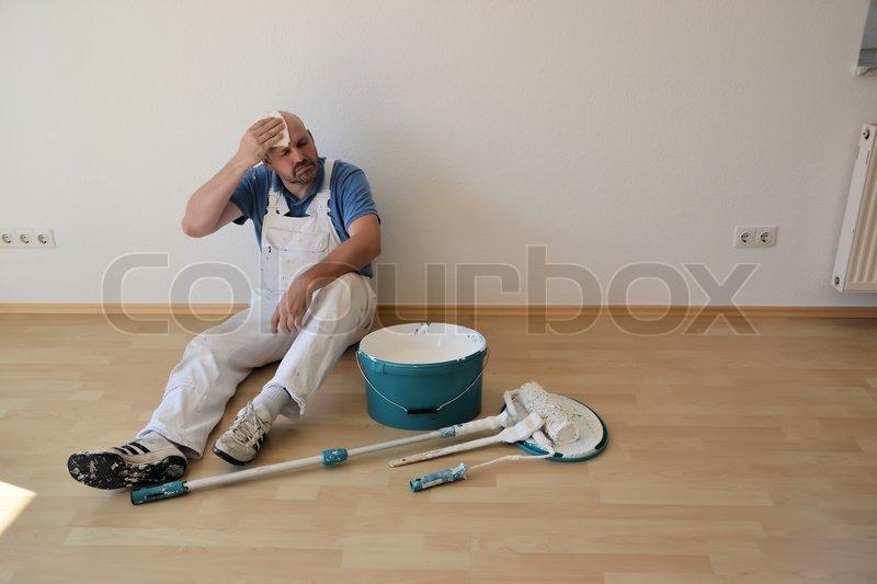 Maler bei der arbeit  Ein Maler nach der Renovierung einer Wohnung auf einer Baustelle ...