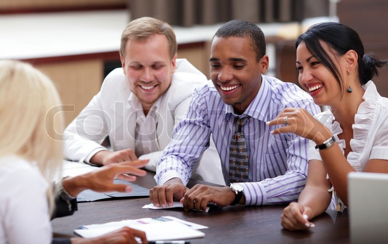 Happy business people sitting around the table at the meeting, stock photo