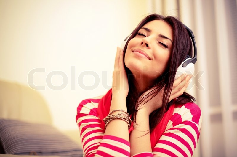 Young beautiful woman in bright outfit enjoying the music at home, stock photo