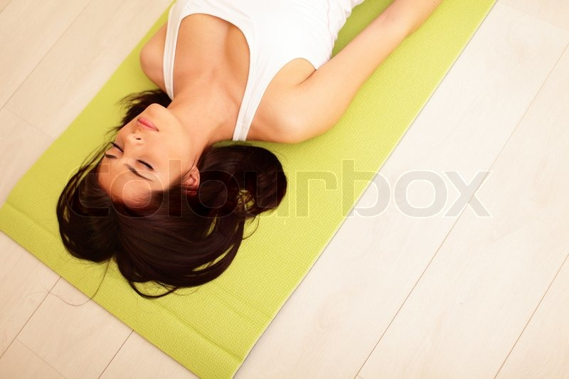 Young woman in sport cloths lying on the yoga mat, stock photo