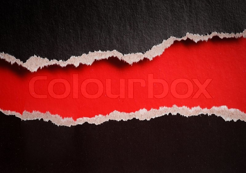 Red hole with torn edges in black paper, stock photo