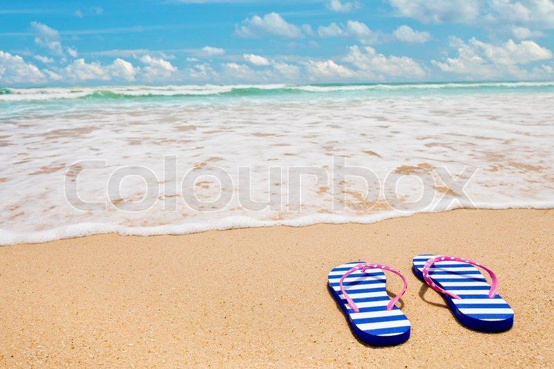 fcb12517d8b2d Colorful striped sandals on sea beach