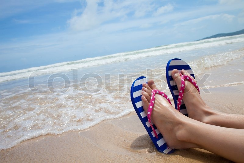 0ff97caf19b6f Young girl legs in colorful flipflop sandals on sea beach