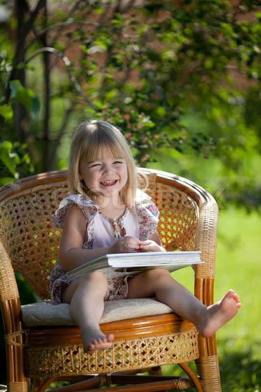 Little Girl Reading Book Sitting In Wicker Chair Outdoor