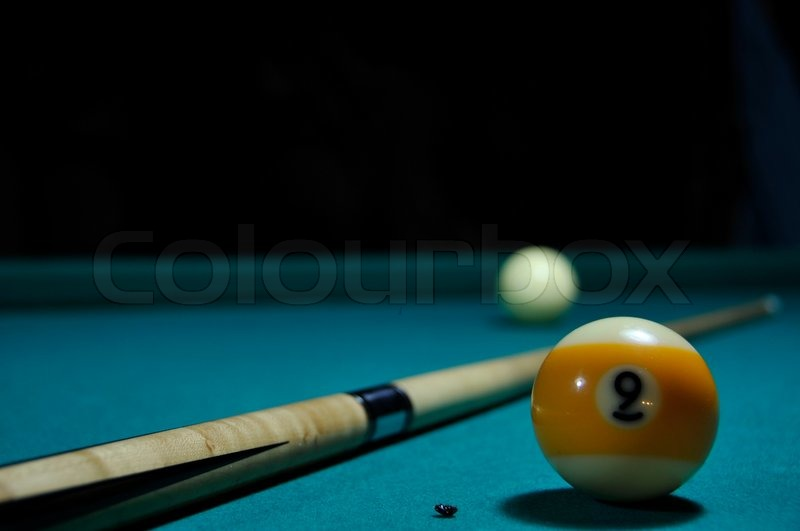 Pool table at night with cue and two balls, stock photo
