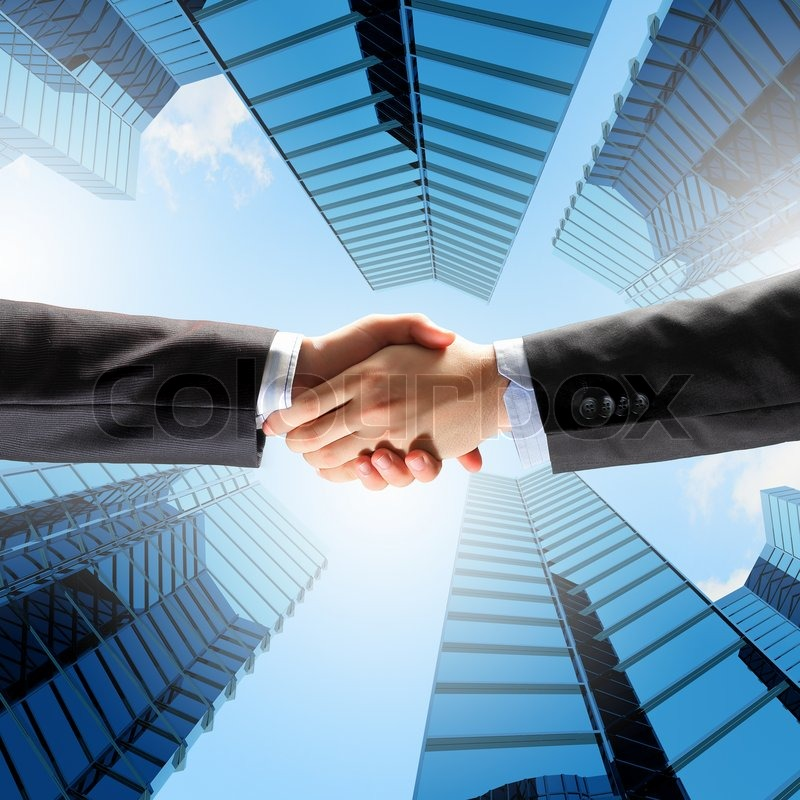 Close up image of hand shake against skyscrapers, stock photo