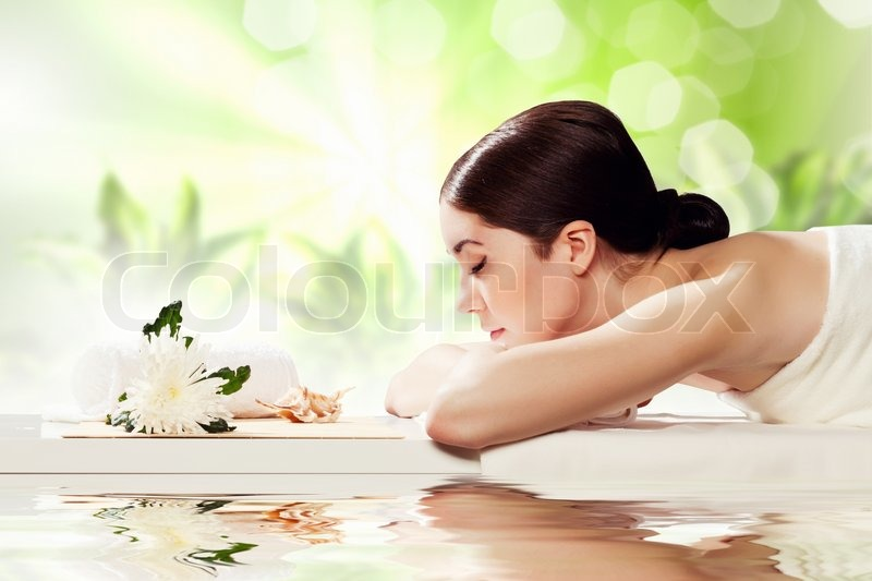 Young pretty woman with clear skin at spa salon getting massage, stock photo