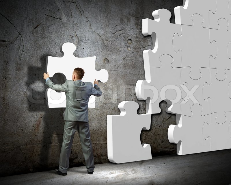 Image of businessman compiling macro white puzzle. Building business, stock photo