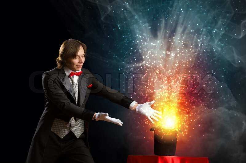 Image of magician holding hat with lights and fumes going out, stock photo
